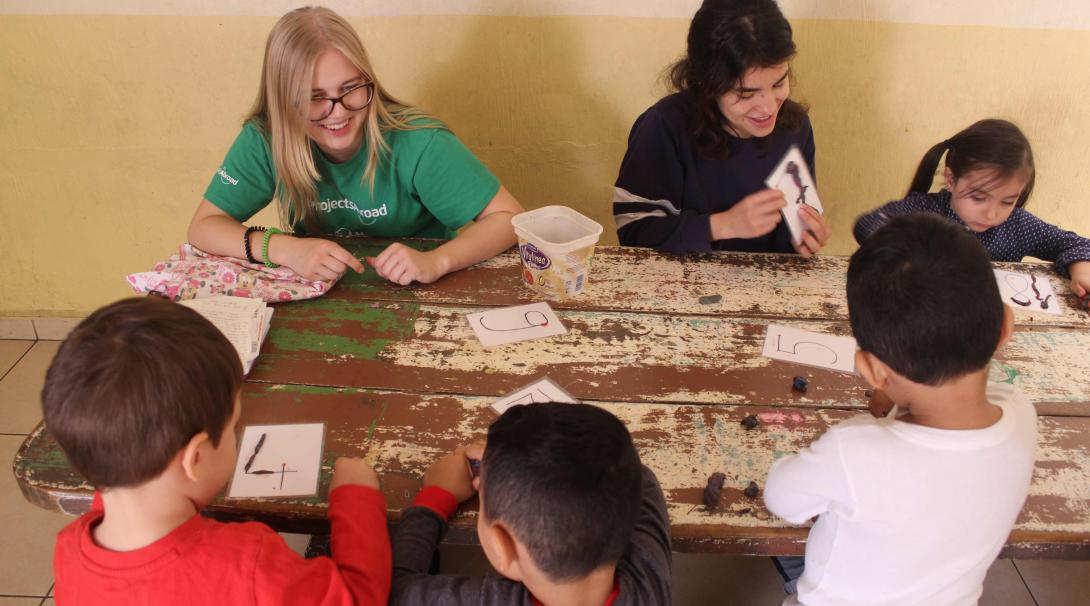 Swiss volunteer Laurane helping to teach the numbers to little children.